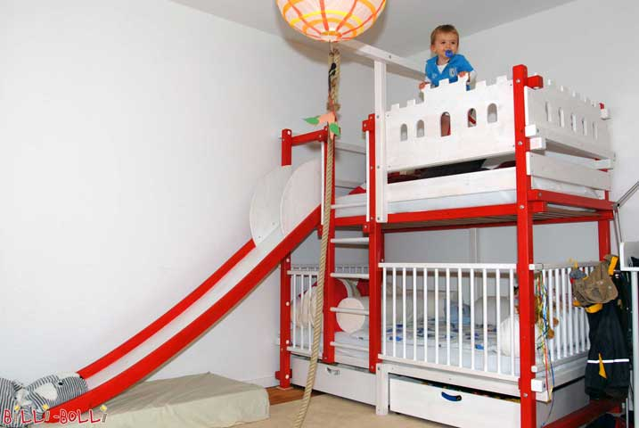 Bunk bed at ladder position B, slide at position A with slide ears, knight's castle boards and baby gates for the lower level, painted by the parents. No wonder, the boy is beaming, right?
