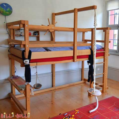 The Low Loft Bed is made of oil-waxed beech and has been equipped with a Play Shop Shelf.