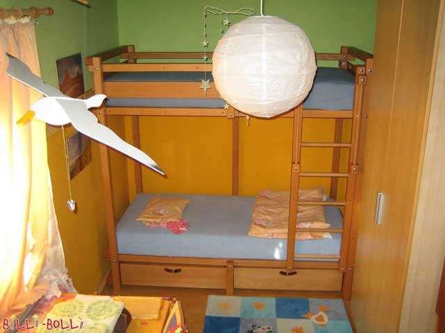The depicted Youth Bunk Bed is made of oil-waxed beech and has two bed drawers.