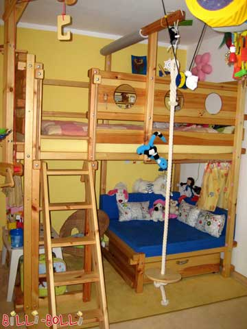 The Comfy Corner Bed is made of pine, with cushion pillows and a mattress for the comfy corner. Additional accessories: porthole theme boards, inclined ladder, play crane and rope with a rocking plate.